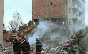 Les pompiers sur les débris d'un immeuble à Mulhouse, après son explosion accidentelle, le 27 décembre 2004.