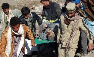 Des Yéménites portent le corps d'une victime des bombardements de l'aviation saoudienne, le 26 mars 2015 à Sanaa