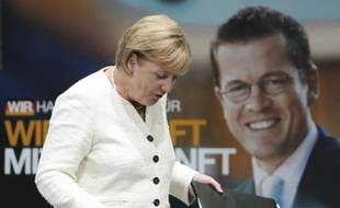 La chancelière allemande, Angela Merkel, devant une affiche électorale sur laquelle figure son actuel ministre de l'Economie Karl-Theodor zu Guttenberg, le 17 août 2009.