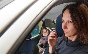 Bordeaux, 27 mars 2013. - Jeune femme fumant au volant en presence d'un enfant. - Photo : Sebastien Ortola