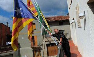 """Avec un sourire fier et provocateur, Jordi Fàbrega, l'édile de Sant Pere de Torelló pose devant le drapeau indépendantiste catalan ornant le bâtiment de la mairie, la première à s'être déclarée """"territoire catalan libre"""" en 2012, en pleine poussée indépendantiste de la Catalogne."""