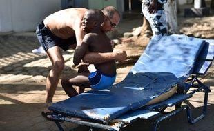 Un homme aide un enfant blessé lors d'une attaque par des gens d'armés de la station balnéaire de Grand-Bassam, en Côte d'Ivoire.