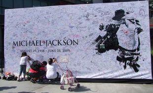 Les fans laissent leur message sur le mur à l'effigie de Michael Jackson, devant le Staples Center de Los Angeles où se déroule, mardi 7 juillet, la cérémonie d'hommage.