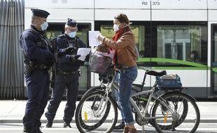 Des policiers contrôlent l'attestation de déplacement d'une cycliste, à Nantes.