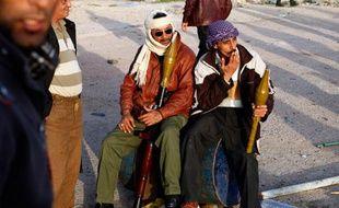 Des opposants patientent à un poste de contrôle avec des lance-roquettes à Brega, Libye, le 3 mars 2011.