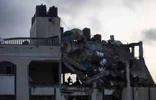 Un Palestinien recherche des survivants sous les décombres d'un toit détruit d'un immeuble résidentiel qui a été touché par des frappes de missiles israéliens, dans le camp de réfugiés de Shati à Gaza, le 11mai 2021.