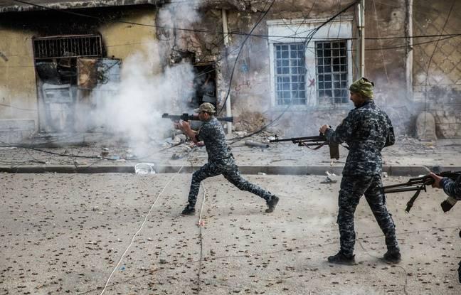 La police fédérale tire sur des positions de l'État islamique au bout d'une rue dans la vieille ville de Mossoul.