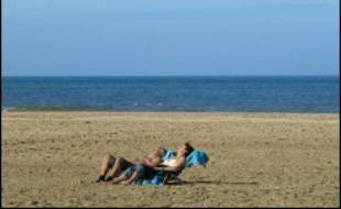 Un couple prend un bain de soleil sur la plage de Deauville