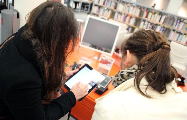 Deux jeunes femmes utilisent une tablette à la bibliothèque des Champs Libres à Rennes.