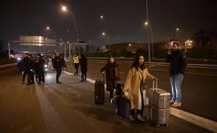Des voyageurs chargés de bagages passent devant des CRS lors d'une action des chauffeurs de VTC près de l'aéroport d'Orly, le 17 décembre 2016.