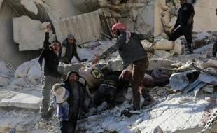 Des civils et des secouristes cherchent des victimes dans les décombres d'un bâtiment à la suite de frappes aériennes gouvernementales à Alep le 7 décembre 2015