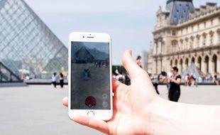Pokemon GO face à la pyramide du Louvre à Paris. EVA FERRE MUR/SIPA