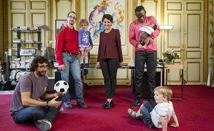 Najat Vallaud-Belkacem, ministre des Droits des femmes et porte-parole  du gouvernement, pose le 1er juillet 2013 dans son bureau avec 3 pères  de famille dans le cadre de la présentation prochaine d'un projet de loi  sur la parité homme-femme pour les congés parentaux.