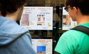 Deux jeunes étudiants regardent les annonces de location d'une agence immobiliere