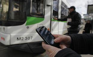 NANTES, le 15/03/2013 Une personne travaille sur son telephone portable avant de monter dans le tram