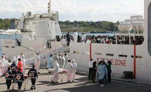 Des migrants se préparent à sortir du beateau de la marine italienne, dans le port de Brindisi, venu les secourir au large de la Sicile, le 15 septembre 2014