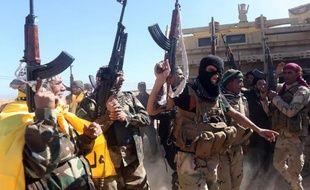 Des forces irakiennes se réjouissent à leur entrée dans la ville de Tikrit, qu'elles cherchent à reprendre aux jihadistes depuis plus d'une semaine, en Irak, le 11 mars 2015
