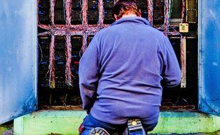 Un technicien devant un central téléphonique. Illustration.