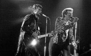 Les chanteurs Johnny Hallyday (g) et Eddy Mitchell sur la scène du 9ème Printemps de Bourges, le 1er avril 1985