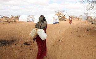 Une réfugiée somalienne porte des jerricans d'eau dans un camp à la frontière avec le Kenya, en avril 2011.