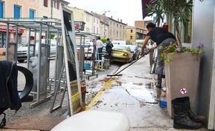 Une commerçante nettoie son magasin, dimanche, à Saint-Gilles.