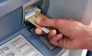 Retrait d'argent avec carte bancaire (image d'illustration).