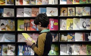 Un enfant lit un livre au Salon de la littérature jeunesse de Montreuil, en 2014.