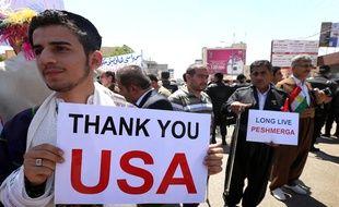 Des chrétiens et des Kurdes d'Irak brandissent des  pancartes remerciant les Etats-Unis, dans la province d'Arbil dans le nord du pays.