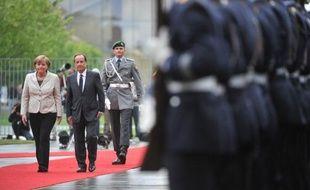 Après la pluie parisienne juste après son intronisation mardi matin, le crachin berlinois attendais François Hollande dans la soirée à Berlin où la chancelière Angela Merkel l'a accueilli solennellement pour son premier déplacement à l'étranger.