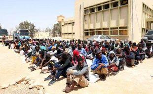 Des migrants d'Afrique subsaharienne attendent devant un centre de rétention à Misrata, dans l'est de la Libye, d'être transférés vers un autre centre, le 9 mai 2015