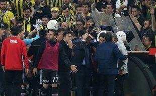 L'entraîneur du Beskitas se prend la tête à deux mains après avoir été heurté par un projectile.