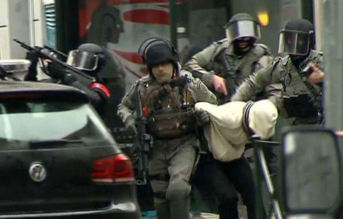 Molenbeek (Belgique), le 18 mars 2016. Des policiers extraient un suspect qui pourrait être Salah Abdeslam. – AP/SIPA