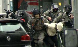 Molenbeek (Belgique), le 18 mars 2016. Des policiers extraient un suspect qui pourrait être Salah Abdeslam.