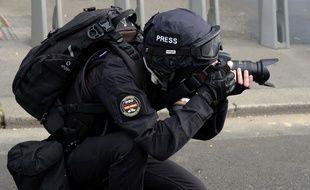 Une personne vêtue de noir avec une casquette siglée presse prenant des photos, le 20 avril 2019 à Paris lors d'une manifestation de