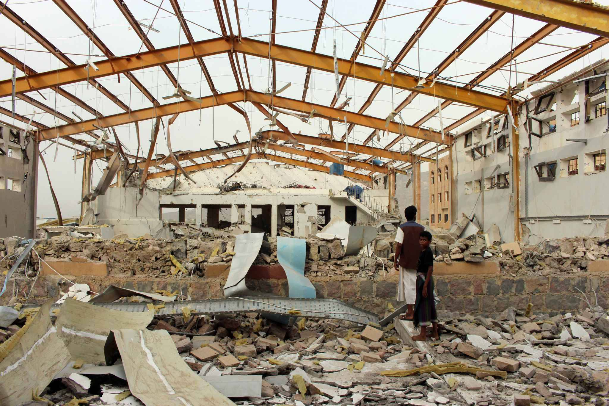 Yemenis inspect the damage caused by a Saudi-led air strike on a cholera treatment centrer supported by Doctors Without Borders (MSF) in the Abs region of Yemen on June 11, 2018. MSF said it has temporarily frozen operations in the rebel-held area of northwestern Yemen following the air strike which caused no casualties.