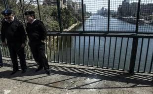 Des policiers égyptiens en faction à l'endroit où une bombe a tué un agent le 5 avril 2015, sur le Pont du 15 mai qui enjambe le Nil au Caire