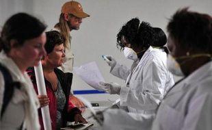 Du personnel médical aide les voyageurs à remplir des formulaires médicaux avant un dépistage du virus Ebola à leur arrivée à l'aéroport international Kenyatta à Nairobi le 14 août 2014