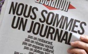 """Un homme lit le journal Libération samedi 8 février 2014, dont la Une est titrée """"Nous sommes un journal"""", réponse de la rédaction aux propositions des actionnaires qui souhaitent transformer le quotidien en réseau social et espace culturel"""