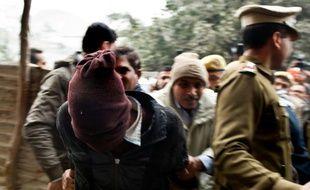 Des policiers indiens (à gauche) escortent un suspect du viol en réunion d'une touriste danoise devant le tribunal de Tis Hazari à New Delhi le 16 janvier 2014