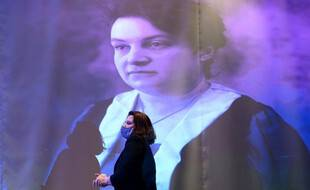 La  ministre déléguée aux Sports, Roxana Maracineanu, passe devant un portrait de l'athlète et pionnière, Alice Milliat, lors de la cérémonie d'inauguration d'une statue hommage à Milliat, à la Maison du sport français qui abrite le Comite national olympique et sportif français, à Paris, le 8 mars 2021.