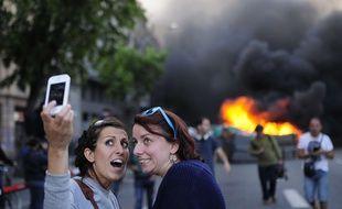 Des touristes font un selfie lors de manifestations houleuses le 1er mai 2014, à Barcelone.