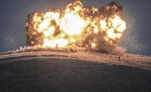 Des membres du groupe Etat islamique devant une explosion lors d'une attaque aérienne le 23 octobre 2014 sur la montagne Tilsehir (Syrie)