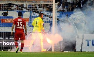 Anthony Lopes, gardien lyonnais ramasse un fumigène lancé sur le terrain à Marseille le 20 septembre 2015