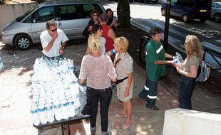 Des volontaires distribuent des bouteilles d'eau dans les rues de Draguignan, le 17 juiin 2010, deux jours après les inondations meurtrières.
