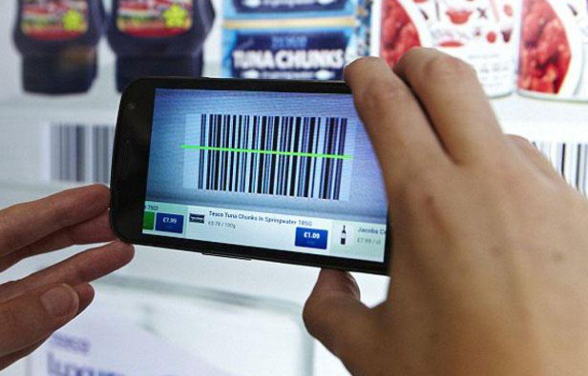 Un voyageur fait ses courses de manière virtuelle à l'aéroport de Gatwick à Londres grâce à son smartphone. – TESCO
