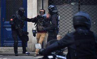 Des policiers anti-émeute se disputent avec un photographe de presse lors d'affrontements avec des manifestants lors d'une manifestation organisée par le mouvement des gilets jaunes à Bordeaux, le 2 février 2019.