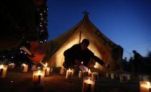 Des réfugiés irakiens chrétiens allument des lumignons de la fête des lumières lyonnaise en l'honneur de la Vierge Marie, apportés par le cardinal Barbarin, le 6 décembre 2014 à Erbil