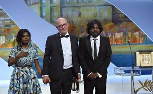 """Jacques Audiard et les acteurs sri-lankais Kalieaswari Srinivasan (gauche) et Jesuthasan Antonythasan après avoir reçu la Palme d'Or pour son film """"Dheepan"""" à Cannes le 24 mai 2015"""