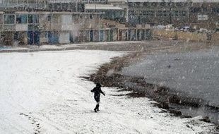Un promeneur sur une plage de Marseille pendant un épisode de neige en 2018