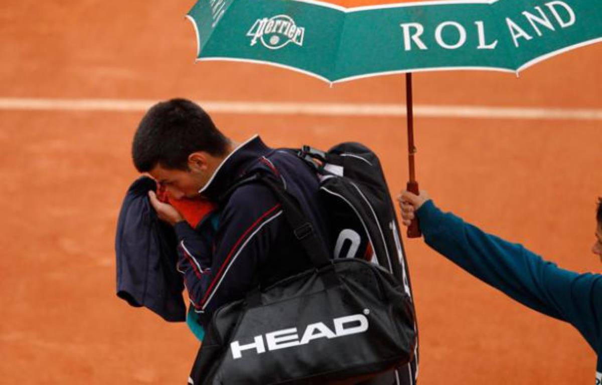 Novak quitte le court de la finale de Roland-Garros sous la pluie, le 10 juin 2012. – no credit